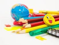 Penne, matite, gomme, con gli smiley e un insieme dei taccuini Immagine Stock