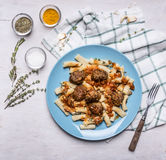 Penne with  meatballs Sicilian by on a blue plate with a fork and spices on a checkered napkin rustic wooden background close u Stock Images