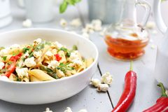 Penne  pasta with asparagus, smoked tofu, chilli peppers and mini corn onions in nut sauce royalty free stock photography