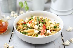 Penne  pasta with asparagus, smoked tofu, chilli peppers and mini corn onions in nut sauce royalty free stock image
