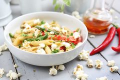 Penne  pasta with asparagus, smoked tofu, chilli peppers and mini corn onions in nut sauce royalty free stock photos