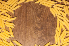 Penne pasta background. Yellow, italian penne pasta, on wooden background Royalty Free Stock Image