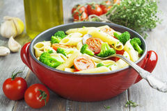 Penne pasta with broccoli and cherry tomatoes Stock Photo