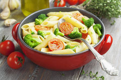Penne pasta with broccoli and cherry tomatoes Stock Images