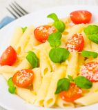 Penne pasta with cheese, tomato and basil Stock Photography