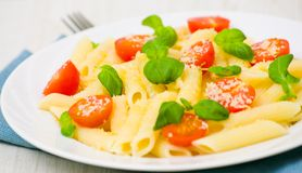 Penne pasta with cheese, tomato and basil Stock Image