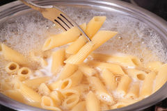 Penne pasta draining. In kitchen Royalty Free Stock Photography