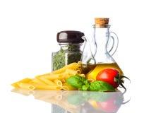 Penne Pasta giallo con italiano che cucina gli ingredienti su fondo bianco Immagini Stock Libere da Diritti