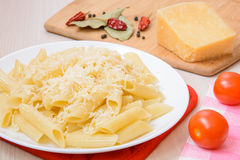 Penne pasta with grated cheese on a white round plate next to the spices and tomatoes on the table. Side view Stock Photo