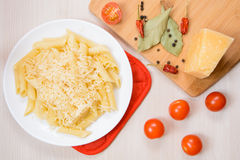 Penne pasta with grated cheese on a white round plate next to the spices and tomatoes on the table. Top view Royalty Free Stock Photography