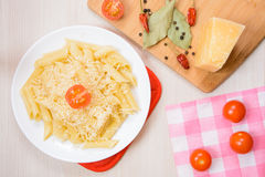 Penne pasta with grated cheese on a white round plate next to the spices and tomatoes on the table. Top view Stock Photos