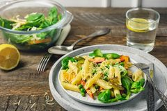 Penne pasta with grilled vegetables. Carrots, pumpkin, pepper and peas stock images