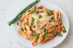 Penne pasta with healthy tuna fish, cheese and chopped scallion or spring onion leaves Stock Photo