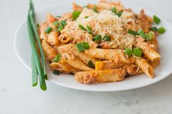 Penne pasta with healthy tuna fish, cheese and chopped scallion or spring onion leaves Stock Photos