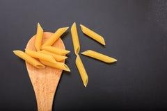 Penne pasta i en slev, svart bakgrund Fotografering för Bildbyråer