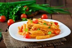 Penne pasta i tomatsås med höna, tomater dekorerade med persilja Royaltyfria Bilder