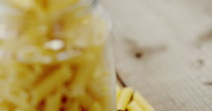 Penne pasta in jar on wooden table. Close-up of penne pasta in jar on wooden table stock footage