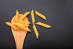 Penne pasta in a ladle, black background. Penne in a wooden ladle, black background Stock Image