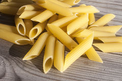 Penne pasta. A lot of yellow penne pasta, on wooden background Royalty Free Stock Image