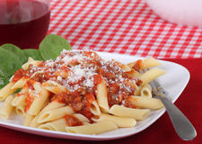 Penne Pasta Meal. Penne pasta topped with tomato meat sauce and parmesan cheese Royalty Free Stock Photo