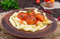 Penne pasta with meat balls in tomato sauce in a clay bowl on a dark wooden background Stock Photography