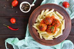Penne pasta with meat balls in tomato sauce in a clay bowl on a dark wooden background. Royalty Free Stock Photography