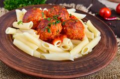 Penne pasta with meat balls in tomato sauce in a clay bowl on a dark wooden background Royalty Free Stock Photo