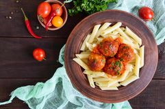 Penne pasta with meat balls in tomato sauce in a clay bowl on a dark wooden background. Stock Photo