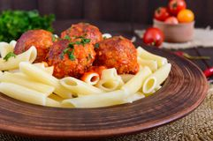 Penne pasta with meat balls in tomato sauce in a clay bowl Stock Photo