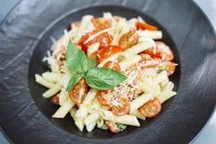 Penne pasta med ost och den körsbärsröda tomaten Arkivbilder