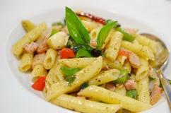 Penne pasta med skinka och basilika, italiensk mat. Arkivfoto