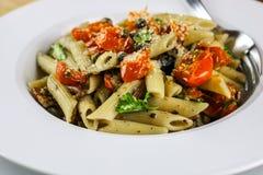Penne Pasta met Geroosterde Cherry Tomatoes, Knoflook en Kappertjes Stock Foto's