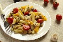 Penne pasta with mushrooms, tomatoes and sweet peppers Stock Photos