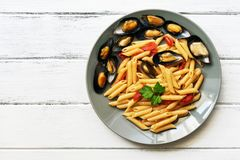 Penne pasta with mussels on a white wooden rustic table. Top view, copy space. stock photography