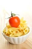 Penne pasta och en Cherrytomat i en liten bunke Arkivbild