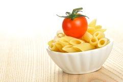 Penne pasta och en Cherrytomat i en liten bunke Royaltyfri Foto