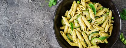 Penne pasta with pesto sauce, zucchini, green peas and basil. I. Talian food. Top view. Flat lay. Banner stock image