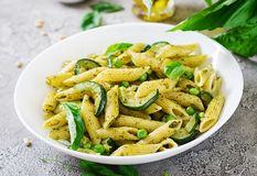 Penne pasta with pesto sauce, zucchini, green peas and basil. royalty free stock photography