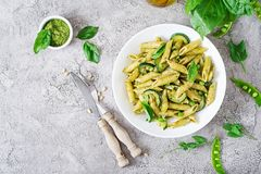 Penne pasta with pesto sauce, zucchini, green peas and basil. royalty free stock images