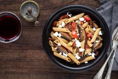 Penne pasta with portobello mushroom and cherry tomatoes. Italian wholemeal or wholegrain penne pasta with portobello mushroom, sun dried tomatoes, cherry stock image
