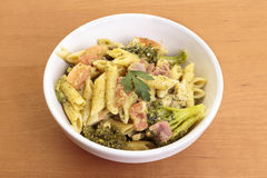 Penne pasta with prosciutto and broccolis. A bowl full of penne pasta with prosciutto and broccolis Stock Photo
