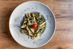 Penne pasta with prosciutto and spinach. Colorful plate with penne pasta with prosciutto and spinach on a table Royalty Free Stock Photography