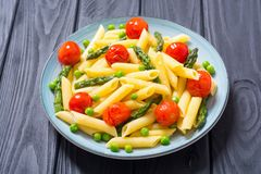 Penne pasta salad with asparagus , tomatoes and peas. Food background royalty free stock photo