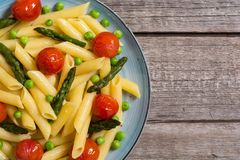 Penne pasta salad with asparagus , tomatoes and peas. Food background stock photos