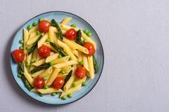 Penne pasta salad with asparagus , tomatoes and peas. Food background stock photo
