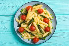 Penne pasta salad with asparagus , tomatoes and peas. Food background royalty free stock photos