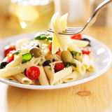 Penne pasta salad. Eating penne pasta salad with fork stock photo
