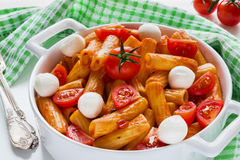 Penne pasta with sauce, mozzarella cheese and cherry tomatoes in casserole on white table Royalty Free Stock Photos