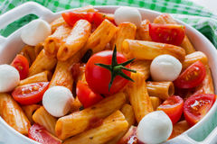 Penne pasta with sauce, mozzarella cheese and cherry tomatoes in casserole on white table royalty free stock image