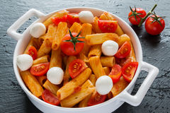 Penne pasta with sauce, mozzarella cheese and cherry tomatoes in white round pan on black stone background Stock Photos
